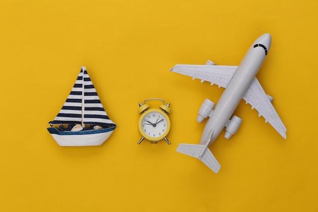 Mini wekker en schip, vliegtuig op een gele achtergrond. tijd om te reizen.