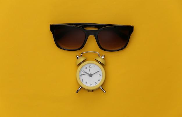 Mini wekker en zonnebril op een gele achtergrond. zomer vakantie tijd.