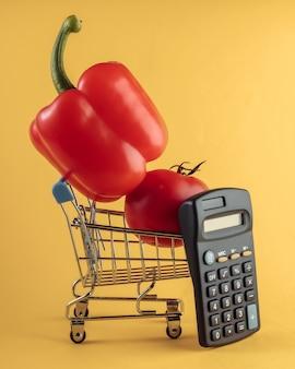 Mini winkelmandje met paprika, tomaat en rekenmachine op geel.
