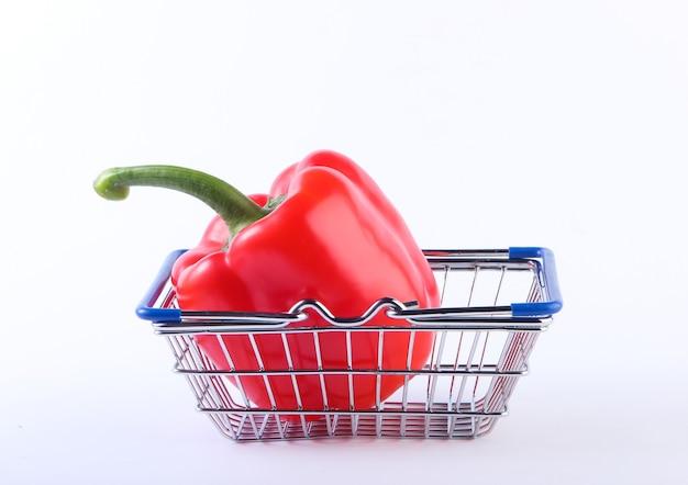 Mini winkelmandje met rode paprika op een wit