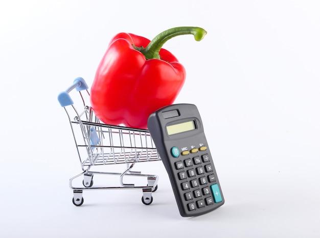 Mini winkelwagen met paprika en rekenmachine op wit