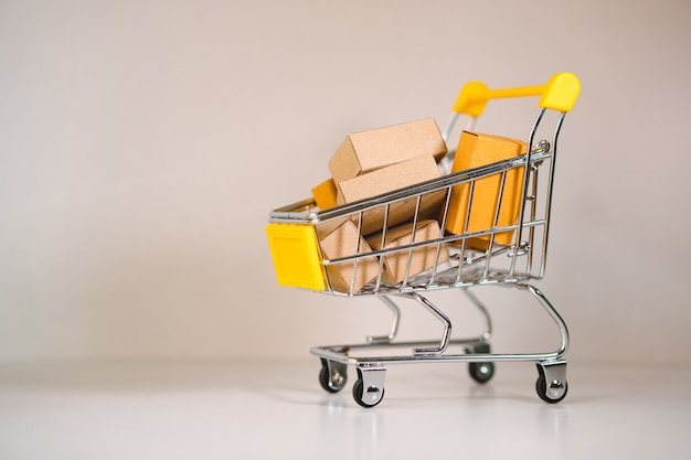 Mini-winkelwagentje bevat papieren doos met als e-commerce, online winkelen en business marketing concept