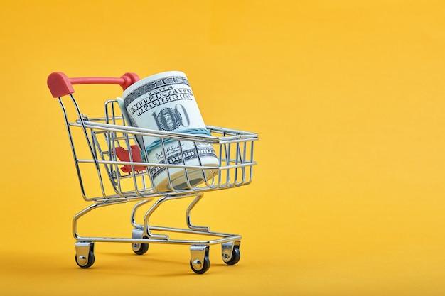 Mini winkelwagentje met 100 dollar biljetten binnen op gele achtergrond trolley en geld