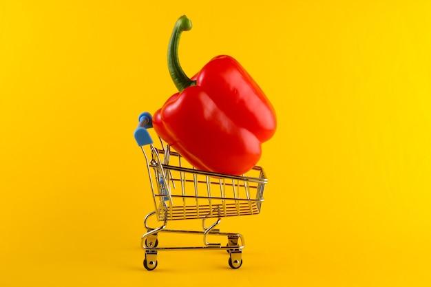 Mini winkelwagentje met paprika op geel. supermarkt concept