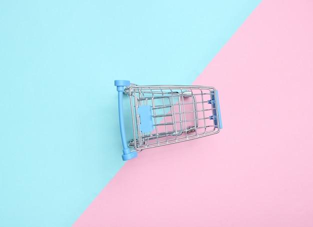Mini winkelwagentje om te winkelen op een gekleurde pasteltafel, consument concept, minimalisme, bovenaanzicht.