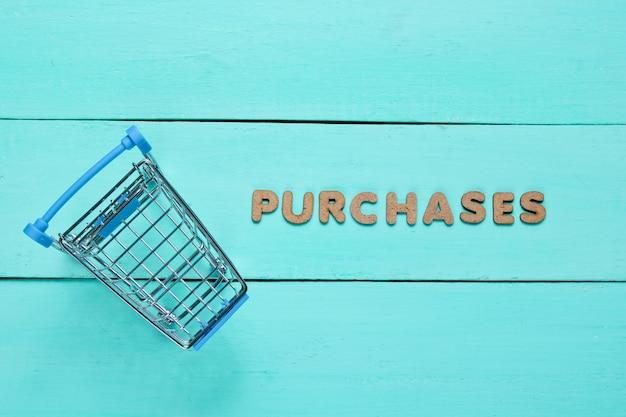 Mini winkelwagentje op blauwe houten oppervlak met het woord aankopen.
