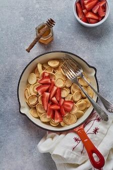 Mini wit pannenkoekgraangewas met aardbeien in koekenpan voor ontbijt op grijze achtergrond