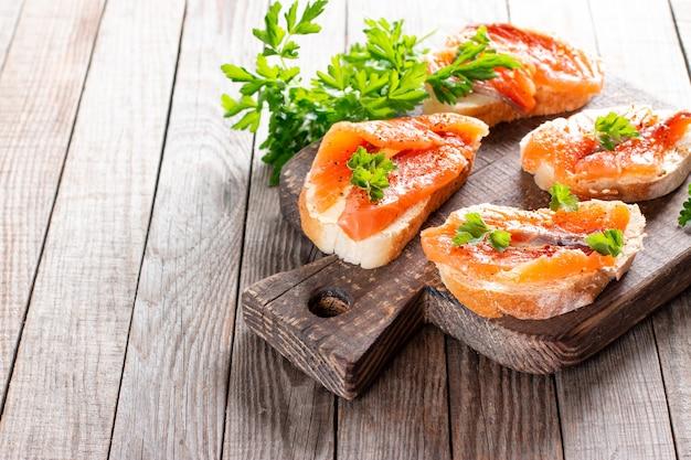 Mini zalmsandwiches op houten bord