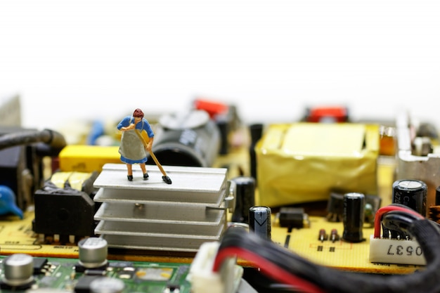 Miniatrische werknemer die moederbordcomputer schoonmaakt.