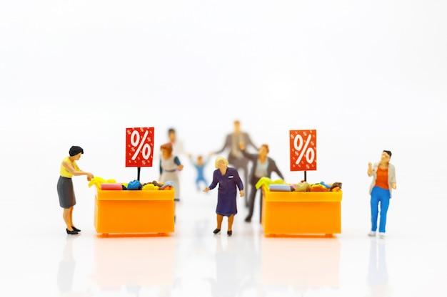 Miniatrue mensen: klanten kopen goederen in de aanbieding met kortingsbonnen.