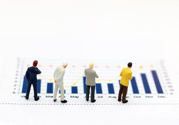 Miniatrue-mensen: zakenman die de grafiek bekijkt.