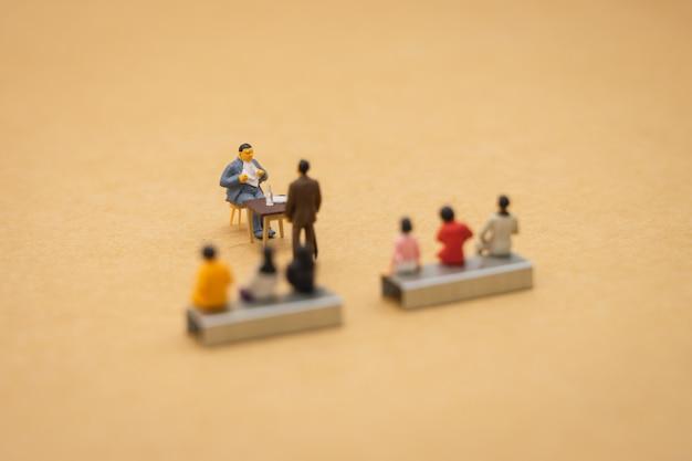 Miniature people businessmen interview kandidaten overweeg om in het bedrijf te werken.