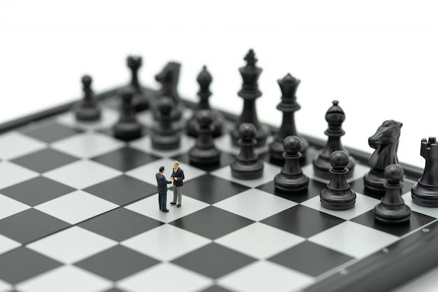 Miniatuur 2 mensen zakenlieden schud de handen op een schaakbord met een schaakstuk