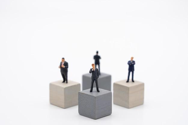 Miniatuur 4 mensenzakenlieden die zich op houten kubiekeinvesteringsanalyse bevinden
