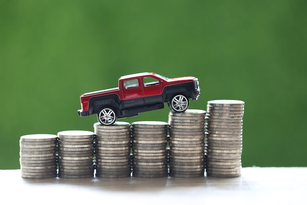 Miniatuur automodel op groeiende stapel munten geld op natuur groene achtergrond, geld besparen voor auto, financiën en autolening, investeringen en bedrijfsconcept