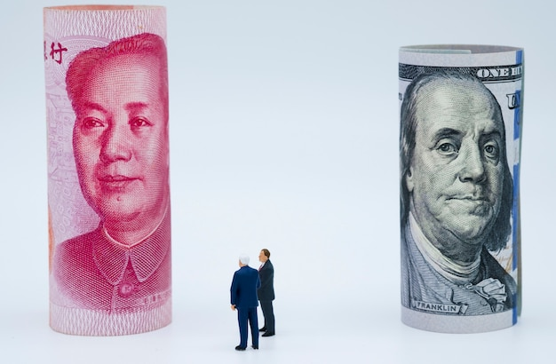 Miniatuur bedrijfsmannen met amerikaanse dollar en china yuan-bankbiljet