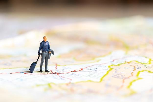 Miniatuur bedrijfsmensen die zich op kaart, reisconcept bevinden