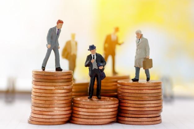 Miniatuur bedrijfsmensen die zich op stap van muntstukgeld bevinden