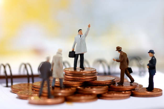 Miniatuur bedrijfsmensen die zich op stap van muntstukgeld bevinden.