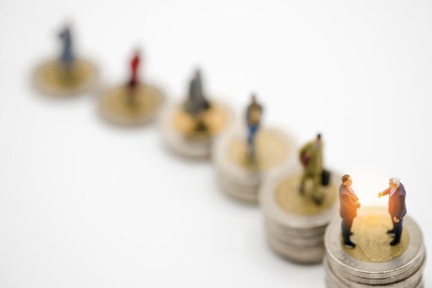Miniatuur bedrijfsmensenmodel op verhoging van het stapelen van muntstukkengeld met witte achtergrond.