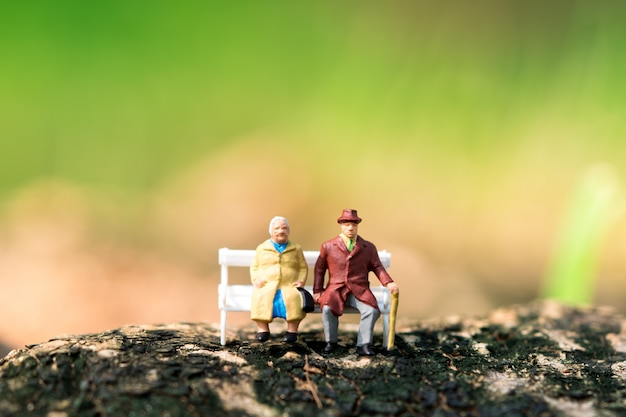 Miniatuur bejaarde mensen die op witte bank zitten die als baanpensionering en verzekeringsconcept gebruiken