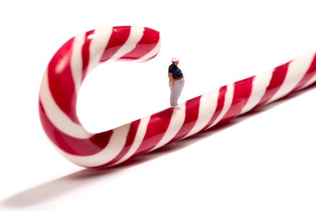 Miniatuur dikke man die op een rode suikerriet