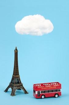 Miniatuur eiffeltoren en toeristische bus op hemelsblauwe achtergrond