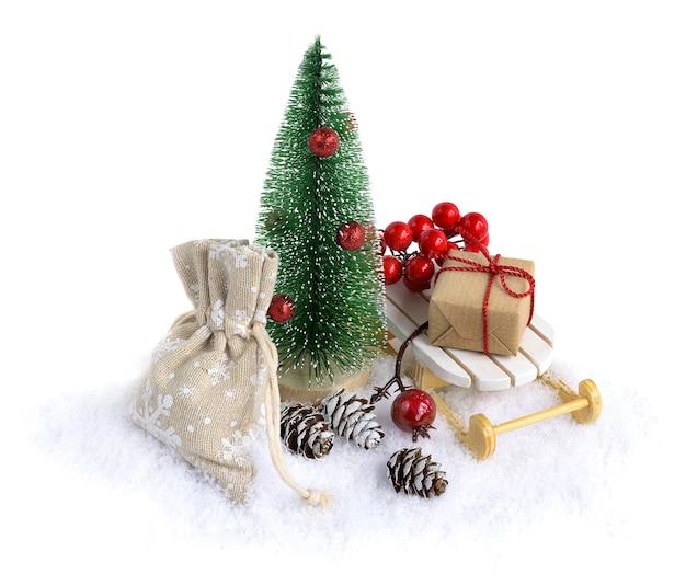 Miniatuur fir tree in sneeuw met kerstcadeaus op de slee geïsoleerd op een witte achtergrond. kerst compositie.