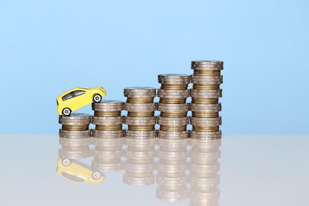 Miniatuur geel automodel bij het kweken van stapel van muntstukkengeld op blauwe achtergrond