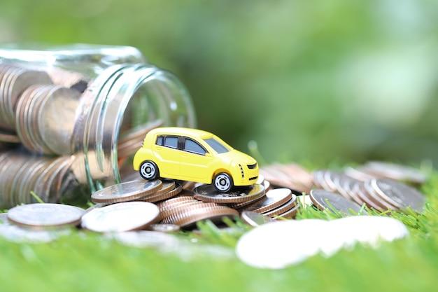 Miniatuur geel automodel op stapel van muntstukkengeld in glasfles op aard groene achtergrond