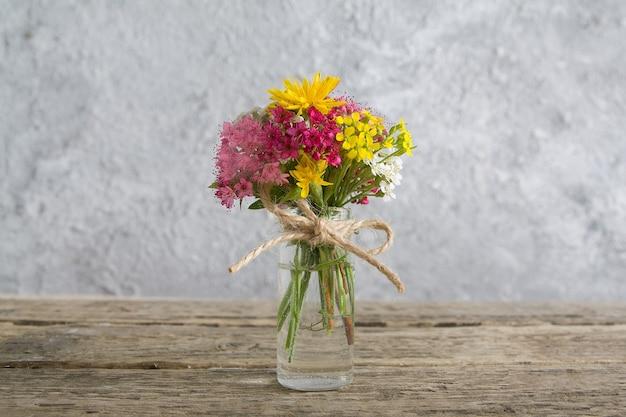 Miniatuur glazen fles met bloemen op houten tafel en betonnen achtergrond
