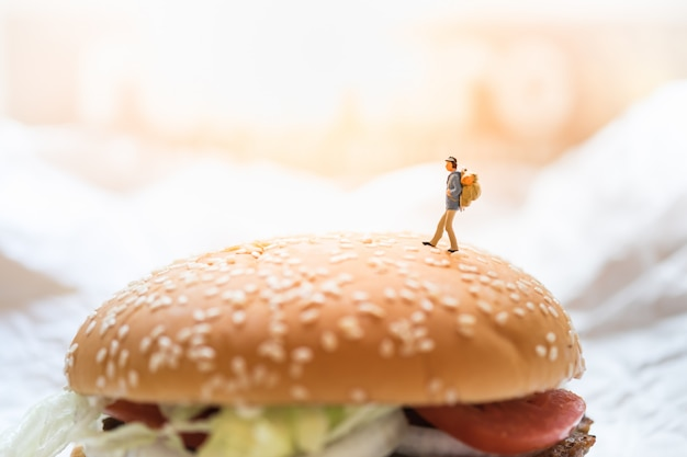 Miniatuur het cijferstuk speelgoed van de reiziger die bovenop de hamburger van het rundvlees lopen.