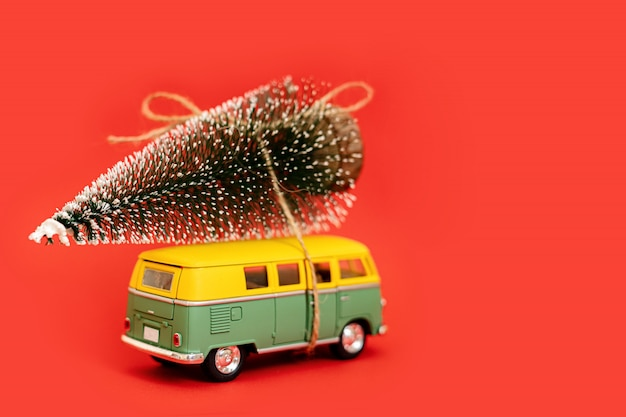 Miniatuur hippie auto met fir tree op rode achtergrond