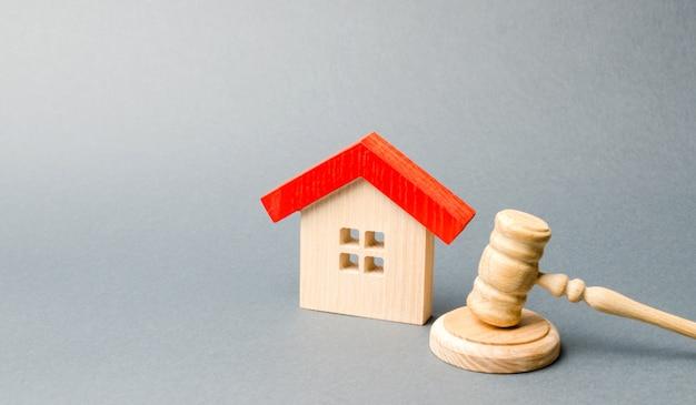 Miniatuur houten huis en de hamer van de rechter.