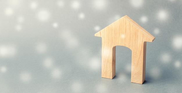 Miniatuur houten huis en sneeuwvlokken. vraag naar onroerend goed in de winter.