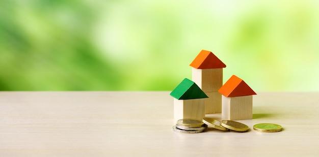 Miniatuur houten huizen en munten op houten tafel en groene natuur achtergrond - investeringen in onroerend goed, onroerend goed ladder, hypotheek concept.