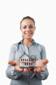 Miniatuur huis dat door jonge vrouwelijke makelaar wordt voorgesteld