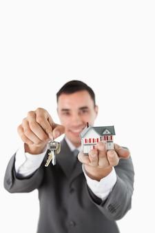 Miniatuur huis en sleutels die door mannelijke landgoedagent worden voorgesteld