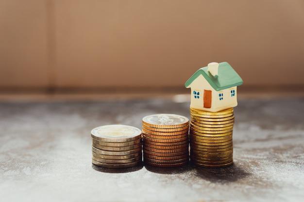 Miniatuur huis op stapel munten