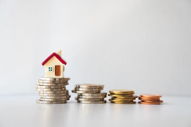 Miniatuur huis op stapelmuntstukken die als bezit en bedrijfsconcept gebruiken