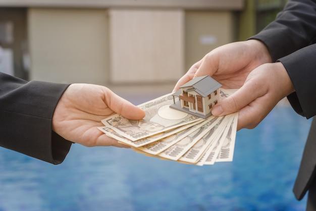 Miniatuur huis speelgoed en geld in iemands handen. hypotheekconcepten. huis en geld