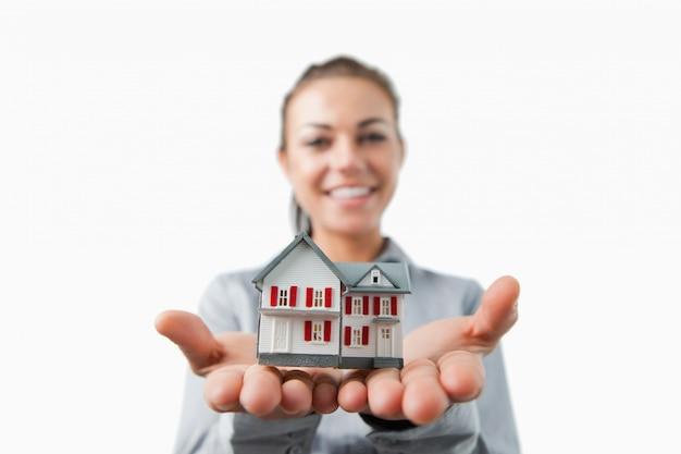 Miniatuur huis wordt gepresenteerd door vrouwelijke makelaar