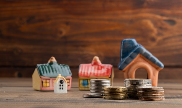 Miniatuur huismodel met munten op hout achtergrond