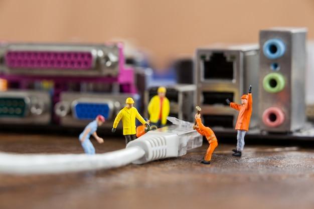 Miniatuur ingenieur en werknemer plug-in lan-kabel op de computer