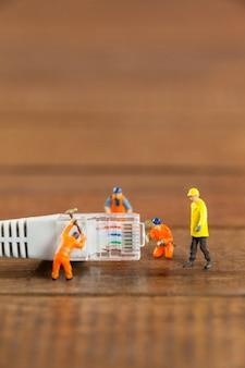 Miniatuur ingenieur en werknemers werken met lan-kabel