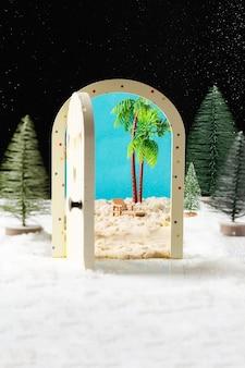 Miniatuur kerstbomen met deur met uitzicht op het strand en palmbomen