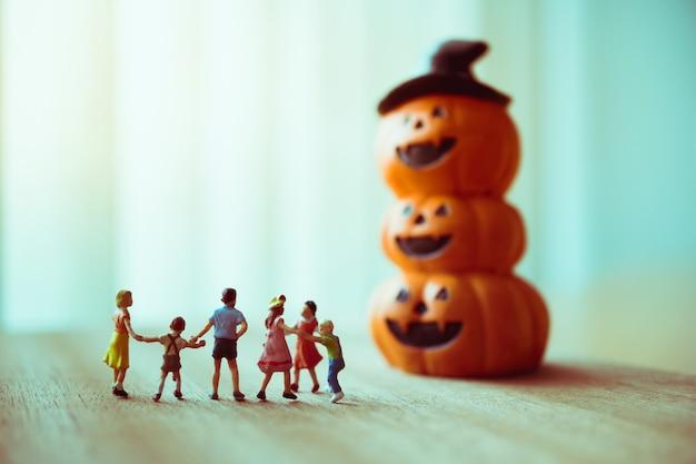 Miniatuur kinderen die spookpompoen bekijken die als familie en halloween-concept gebruiken