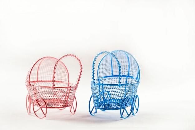 Miniatuur kinderwagens op een wit close-up als achtergrond. baby en zwangerschap concept en kopie ruimte.