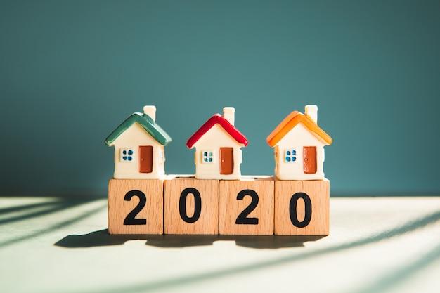 Miniatuur kleurrijk huis op houten blokjaar 2020 die als familie en bezitsonroerende goederenconcept gebruiken