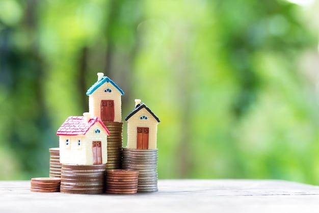 Miniatuur kleurrijk huis op stapelmuntstukken die als bezit en financiënconcept gebruiken